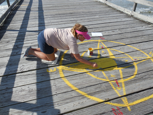 Katie Pipes painting the Sunset Beach Fishing Pier Compass Rose - 2013